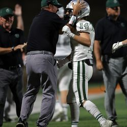 A coach celebrates Sam Kernodle's interception as the Titans and Brighton play a high school football game at Brighton in Cottonwood Heights on Friday, Sept. 10, 2021. Olympus won 35-28.