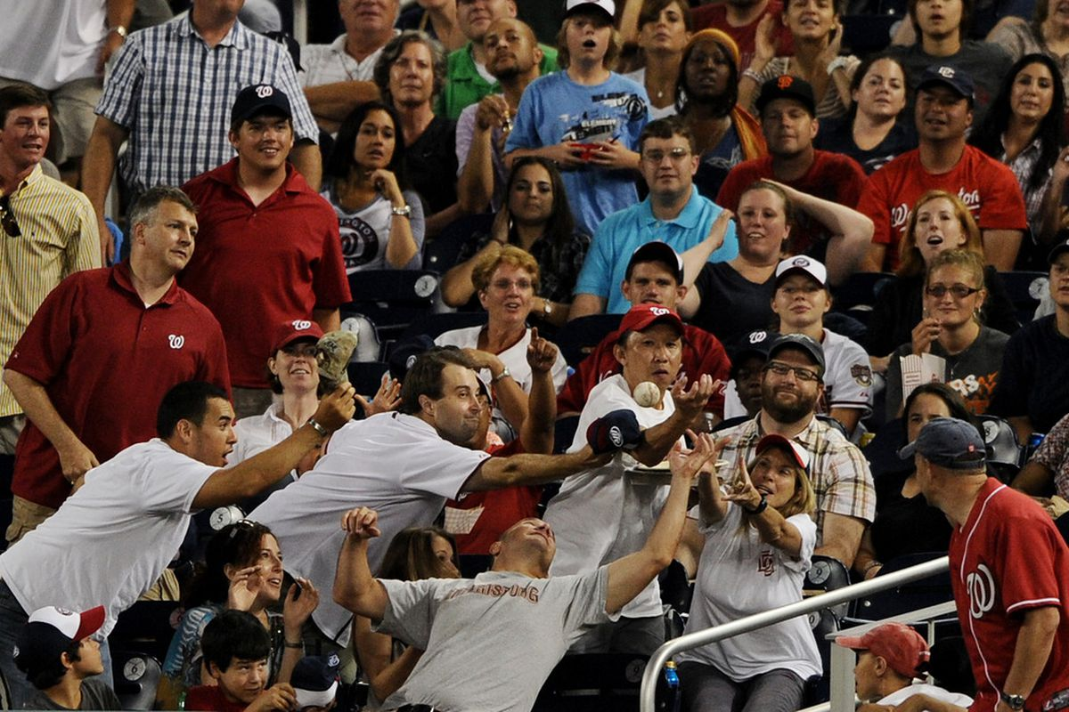 WASHINGTON, DC - JULY 8: Fans reach for a foul ball in the fifth inning as the Washington Nationals play the Colorado Rockies at Nationals Park on July 8, 2011 in Washington, DC. The Colorado Rockies won, 3-2. (Photo by Patrick Smith/Getty Images)