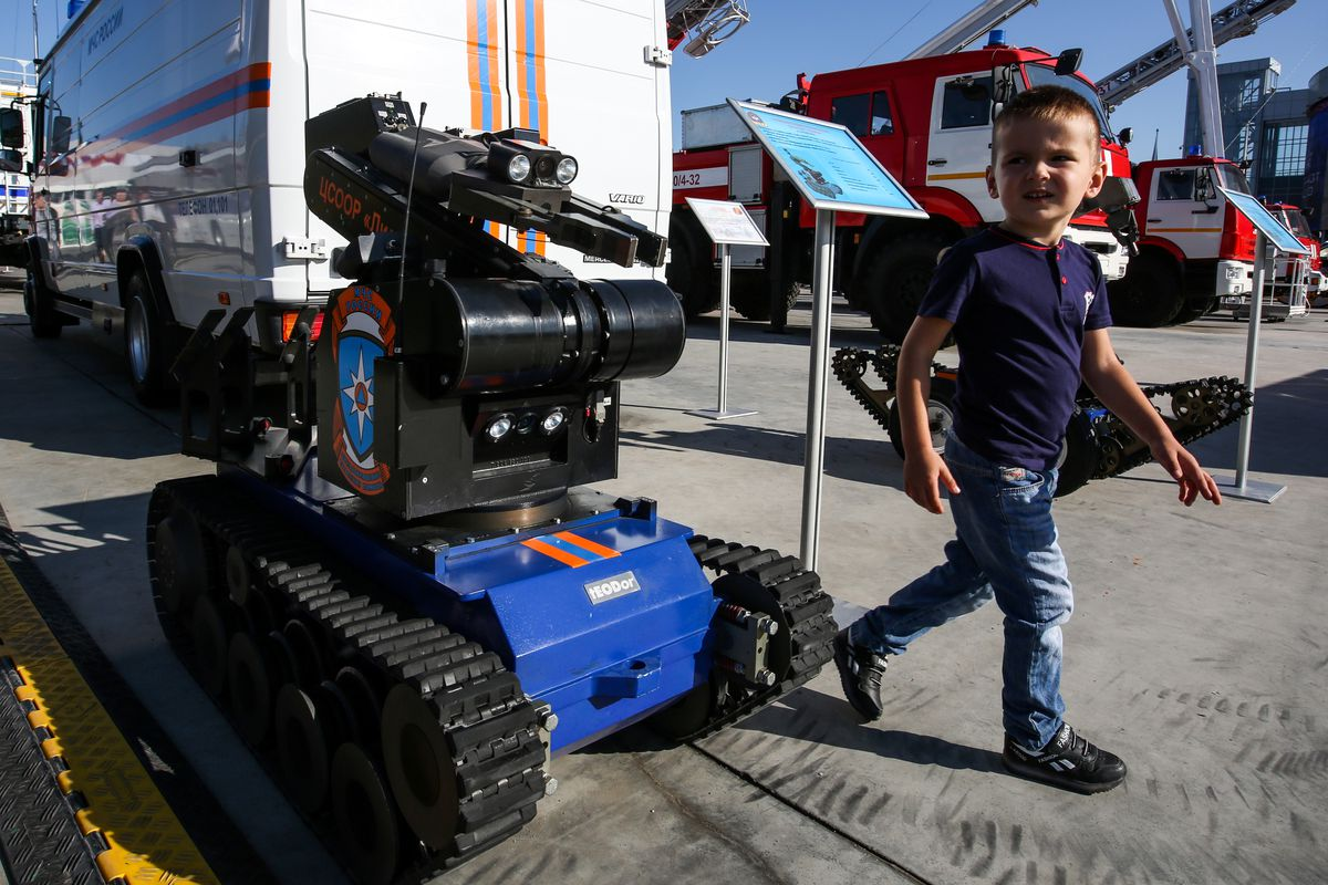 A child walking beside a Telemax robot on tank treads and topped with a gun