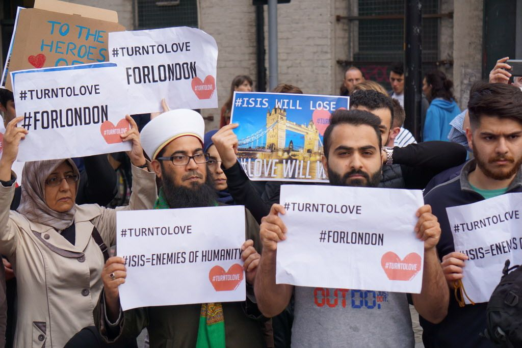 """Muslims hold signs saying """"ISIS WILL LOSE"""" and """"#TURNTOLOVE"""" on Sunday June 4, 2017, at the police cordon surrounding the site in south London of the deadly van-and-knife attack that killed several people on Saturday night.   Raphael Satter/AP"""