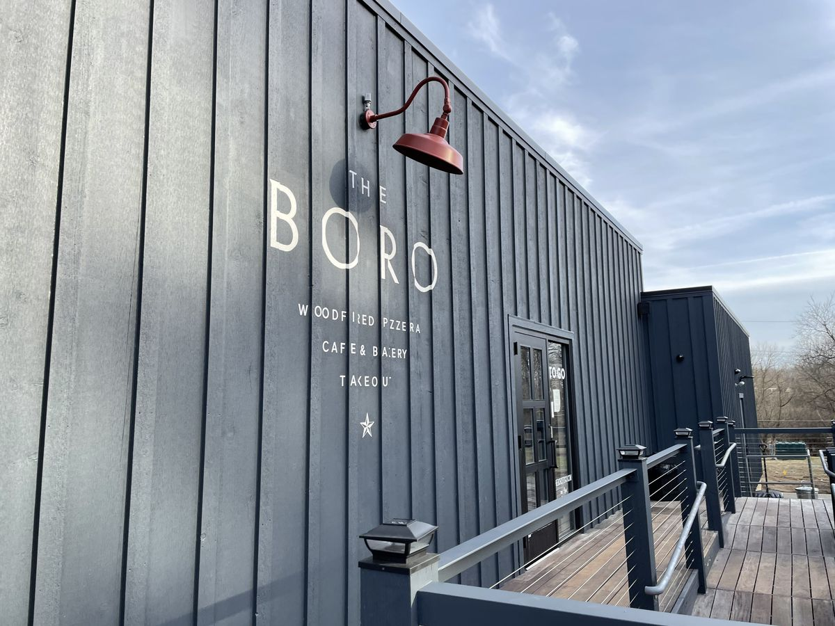 """The gray wooden exterior of the Boro in Ann Arbor with the name of the restaurant """"The Boro"""" painted in white letters on the side of the building. A red metal lamp sits above the name to illuminate it at night"""