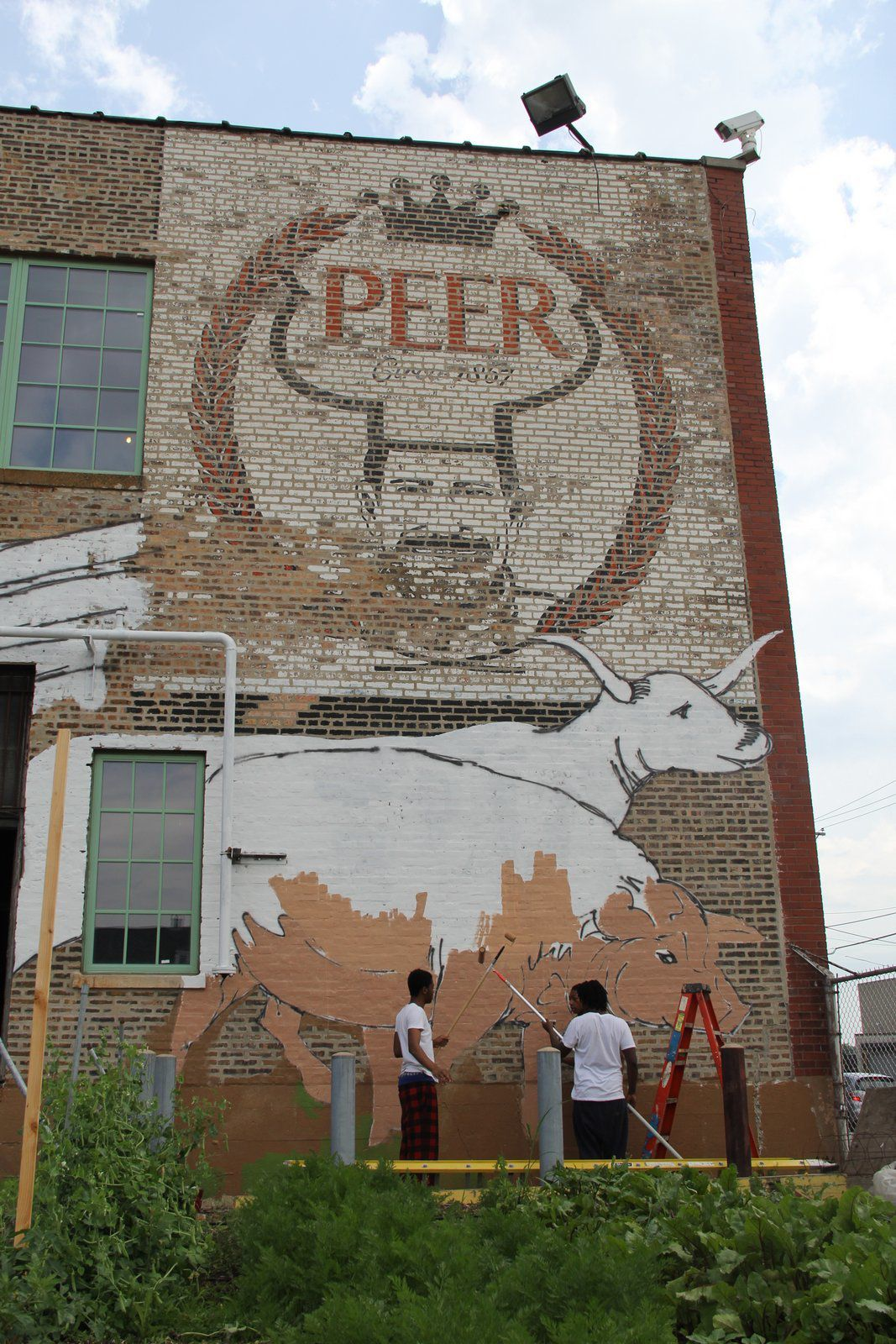 The mural at 1400 W. 46th St., shown here while in progress, incorporates the building's original Peer Foods logo.
