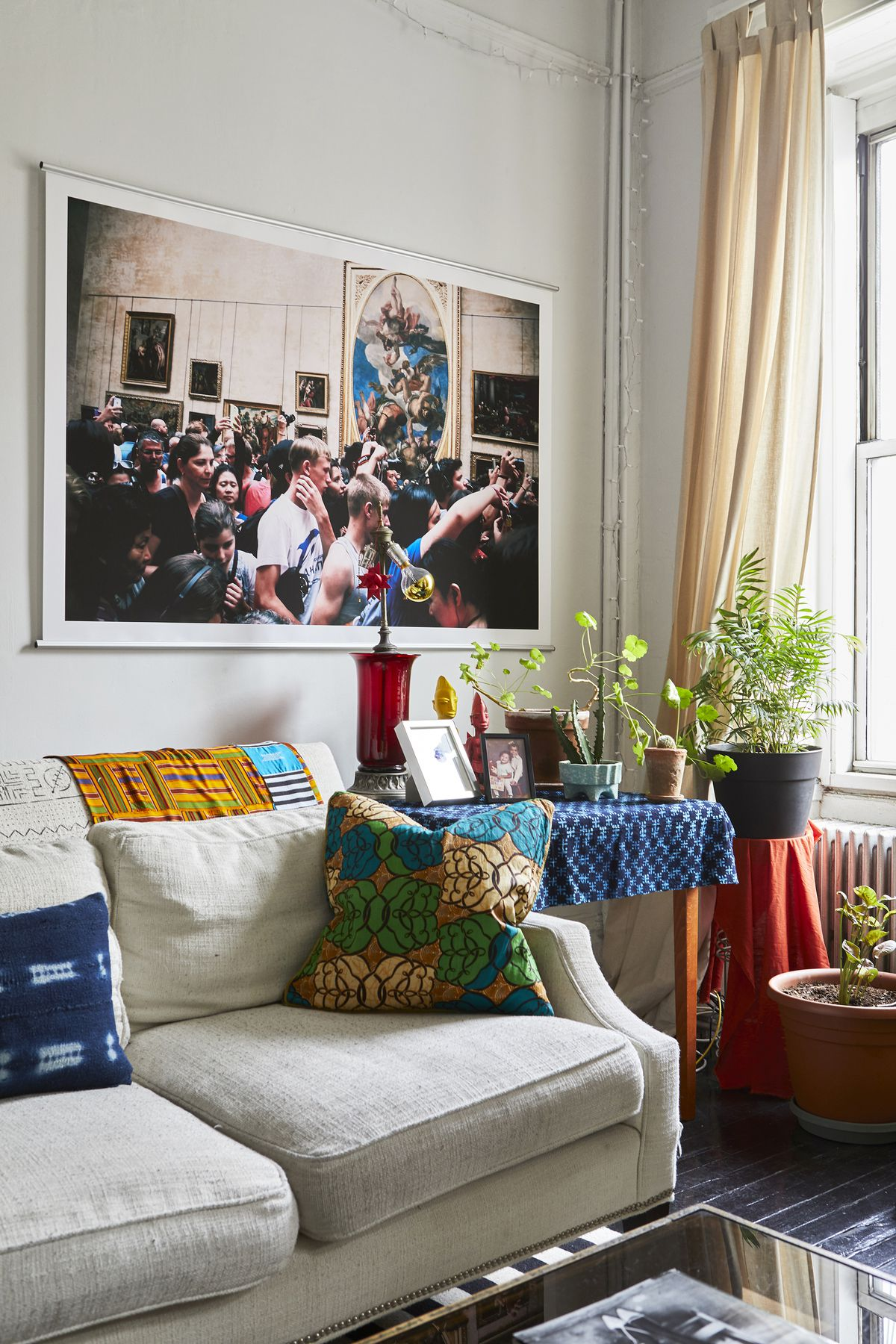 In the living room, a bright photograph hangs over a white sofa.