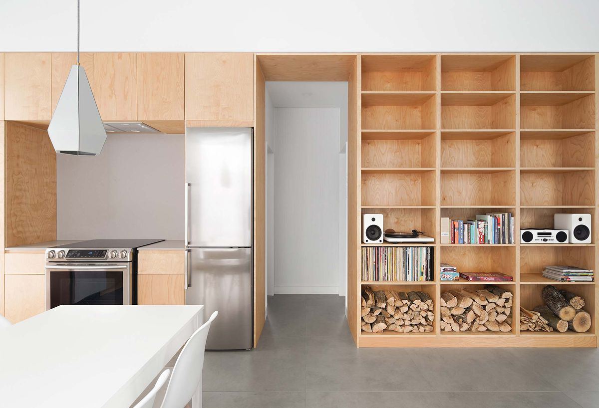 A wall of built-in wooden cabinets, stainless steel appliances, and shelves.