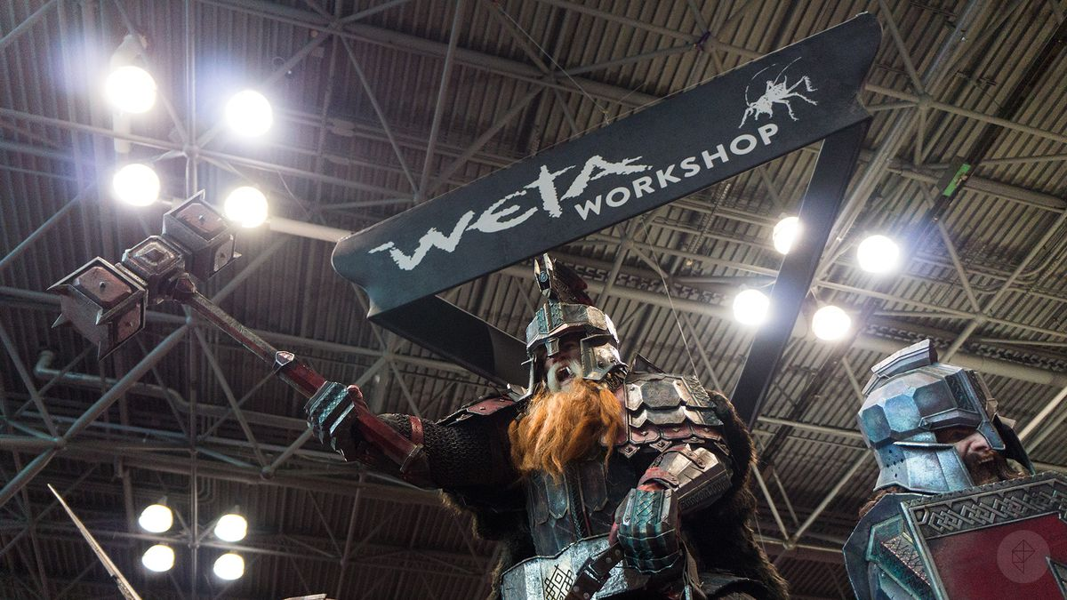 a model of a dwarf wielding a dual-headed mace perched above the Weta Workshop booth at NYCC 2015, with the Weta Workshop banner above it