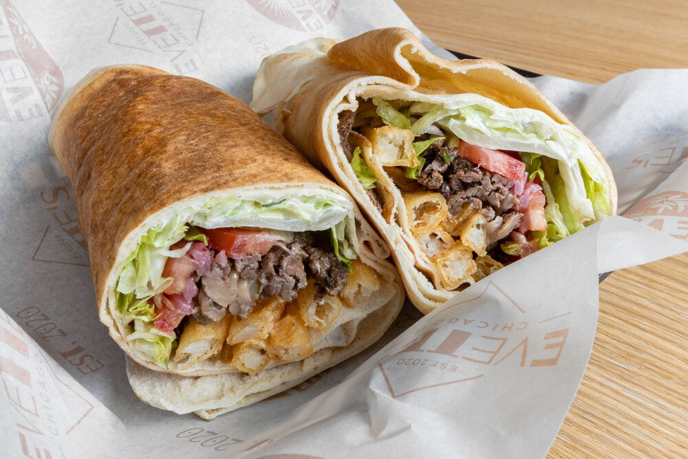 A wrap filled with meat, veggies, and fries.