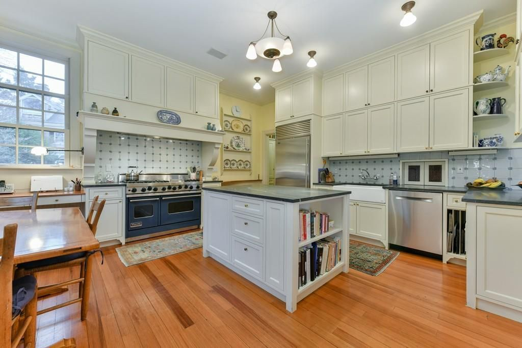 A large kitchen with a large square island and two ovens side by side.