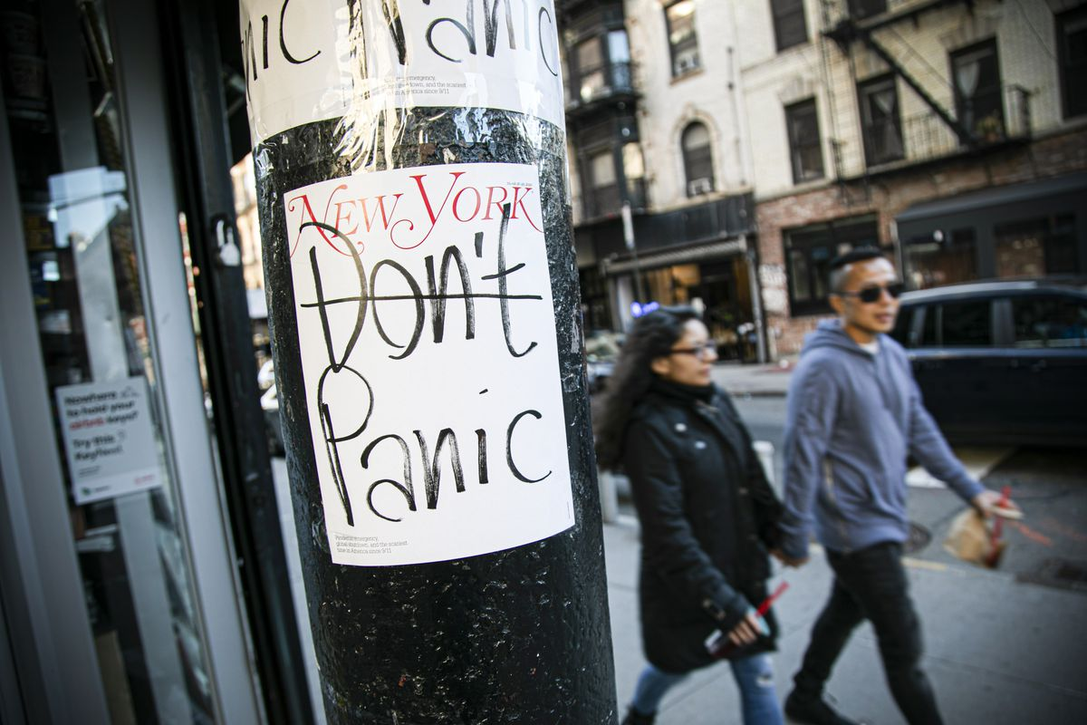 """People walk past a sign that reads """"Don't panic"""" with the """"don't"""" crossed out."""