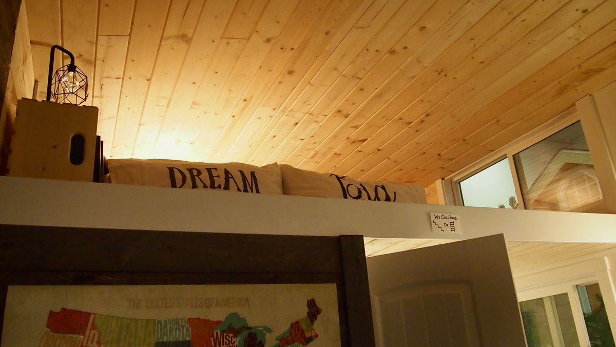 A small loft with pillows under a wood beam ceiling