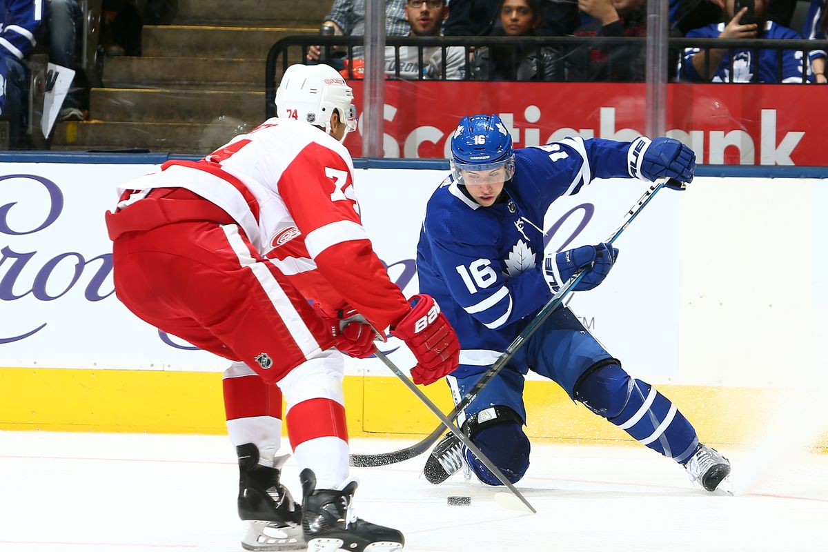 Mitch Marner #16 of the Toronto Maple Leafs battles for the puck with Madison Bowey #74 of the Detroit Red Wings