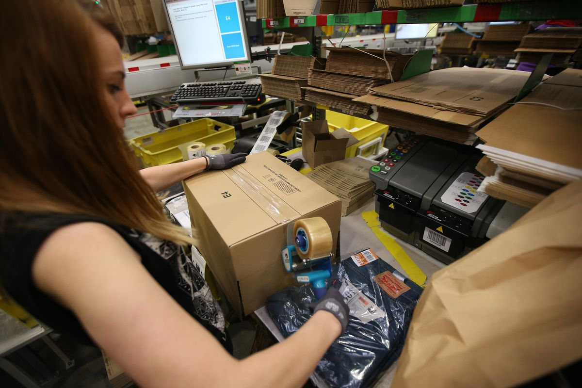 A worker at the Amazon warehouse in Hemel Hempstead, England, tapes up a parcel on December 5, 2014.