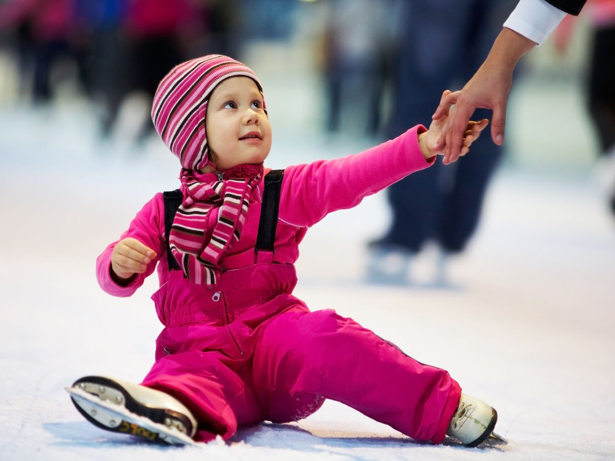 A young child sits on an ice-skating rink, wearing skates.