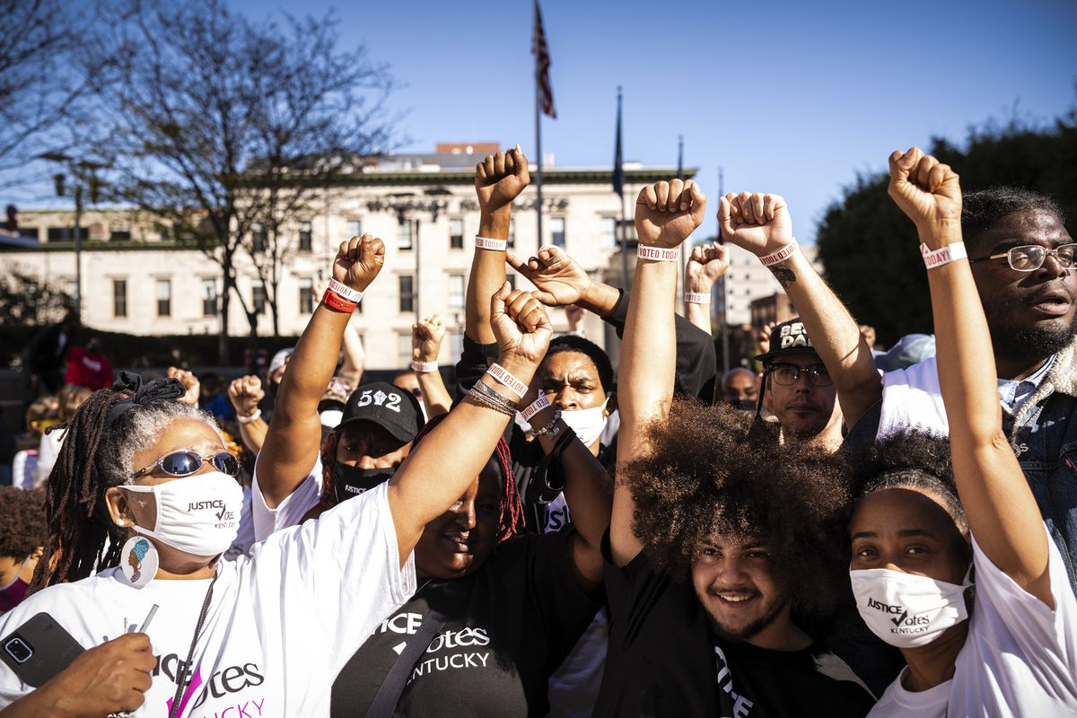 A crowd of about 14 Black people of various skin tones, all of them in either black or white, most of them wearing mask, and of varying age — some look as if they are in college; other have grey hair. All of them have one of their fists raised high, their wristbands visible in the day's bright sun. Behind them is a flagpole flying the US flag.