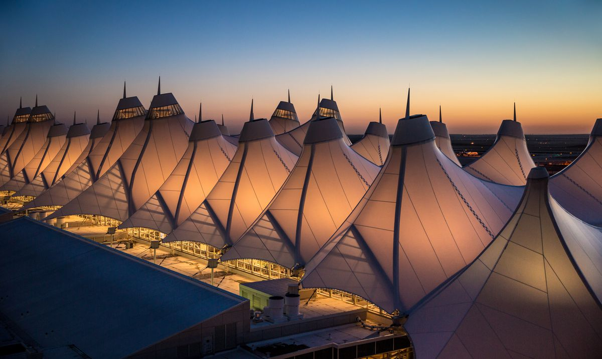 The top of Denver International Airport consists of rows of fabric covered tents. The light from inside the airport is illuminating the tents.
