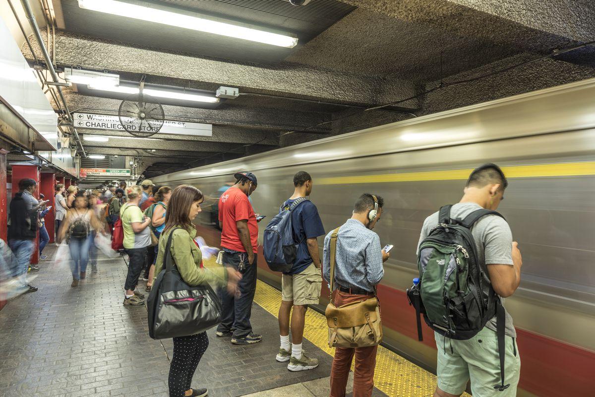 People waiting on a subway platform as a train zooms in.