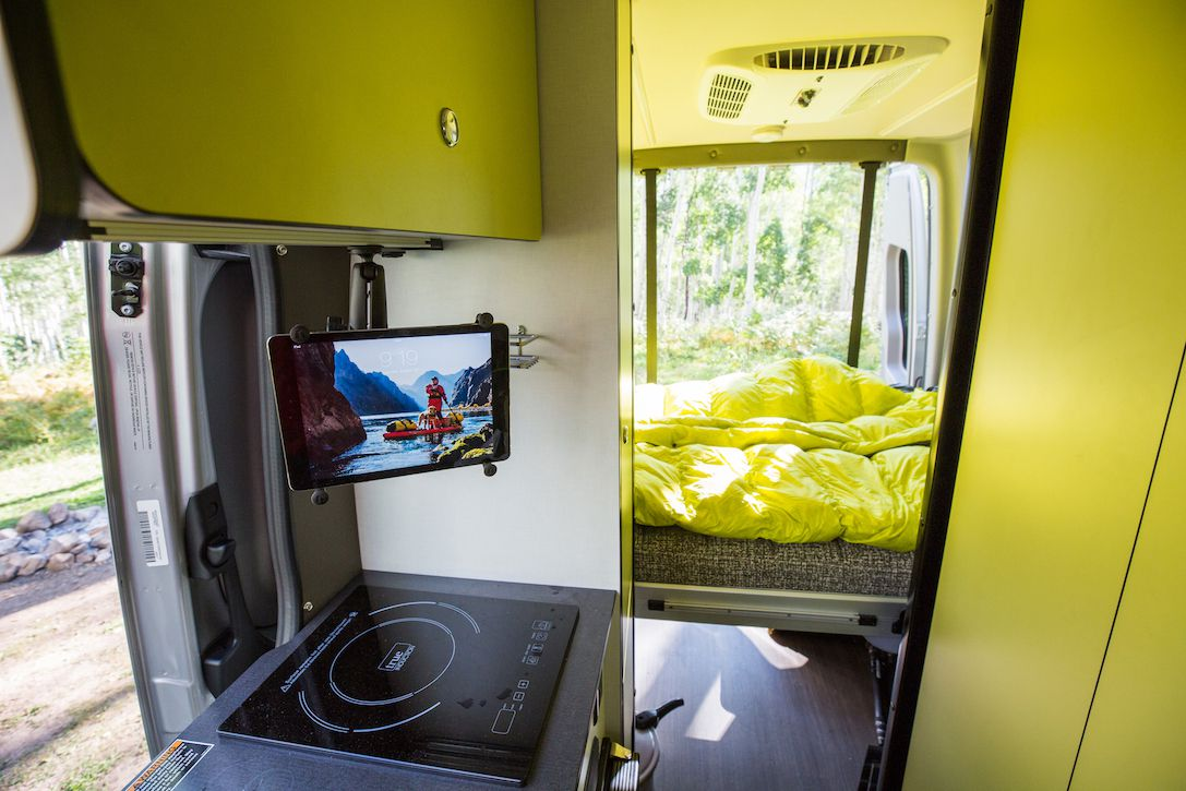 The interior of an RV camper can. In the foreground is a stove. There is a television monitor attached to a cabinet above the stove. In the other room is a bed with lime green bed linens.