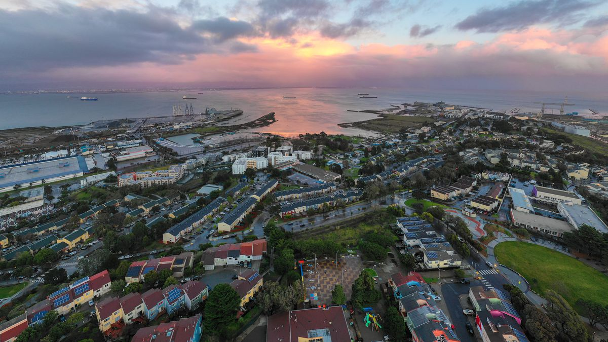 Aerial view of seaside neighborhood with old navy barracks, homes, and industrial spaces. The sun above breaks through a series of clouds.