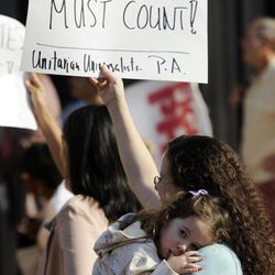 Emily Goldberg and her daughter Willa, 2, holds up a sign during the NAACP voter ID rally to demonstrate the opposition of Pennsylvania's new voter identification law, Thursday, Sept. 13, 2012, in Philadelphia. Pennsylvania's Supreme Court justices are scheduled to hear arguments over whether a new law requiring each voter to show valid photo identification poses an unnecessary threat to the right to vote.