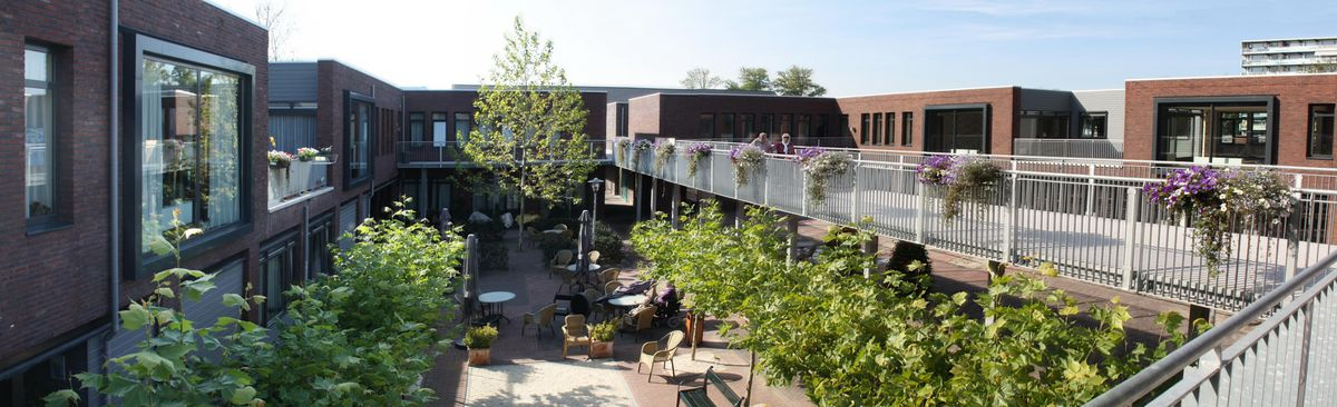 """A patio and common area in between buildings at the Hogeweyk """"dementia village."""""""