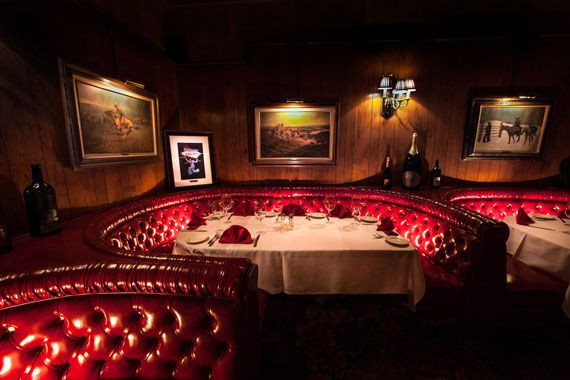 A restaurant interior with red leather booths and photos on the walls.