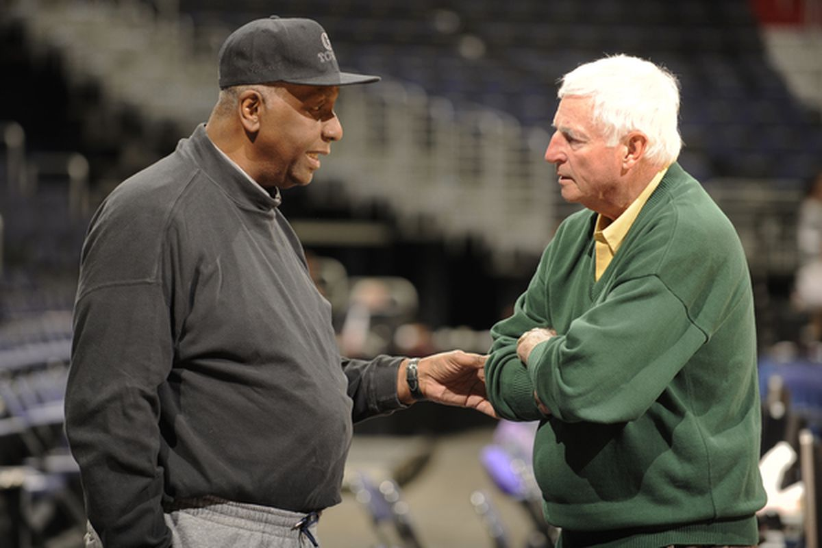 John Thompson discussing events with some guy in a green sweater.  (Photo by Mitchell Layton/Getty Images)