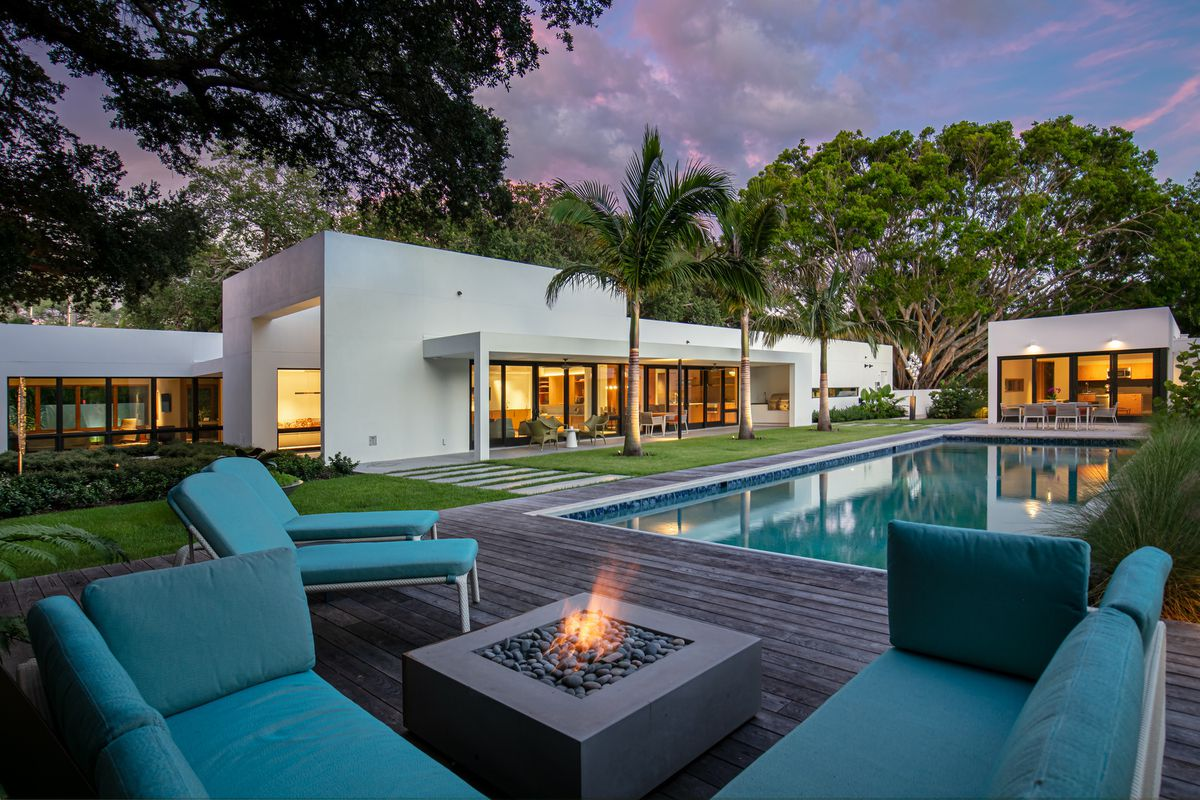 An exterior view of a fire pit and lounge area with a white house and pool in the background.
