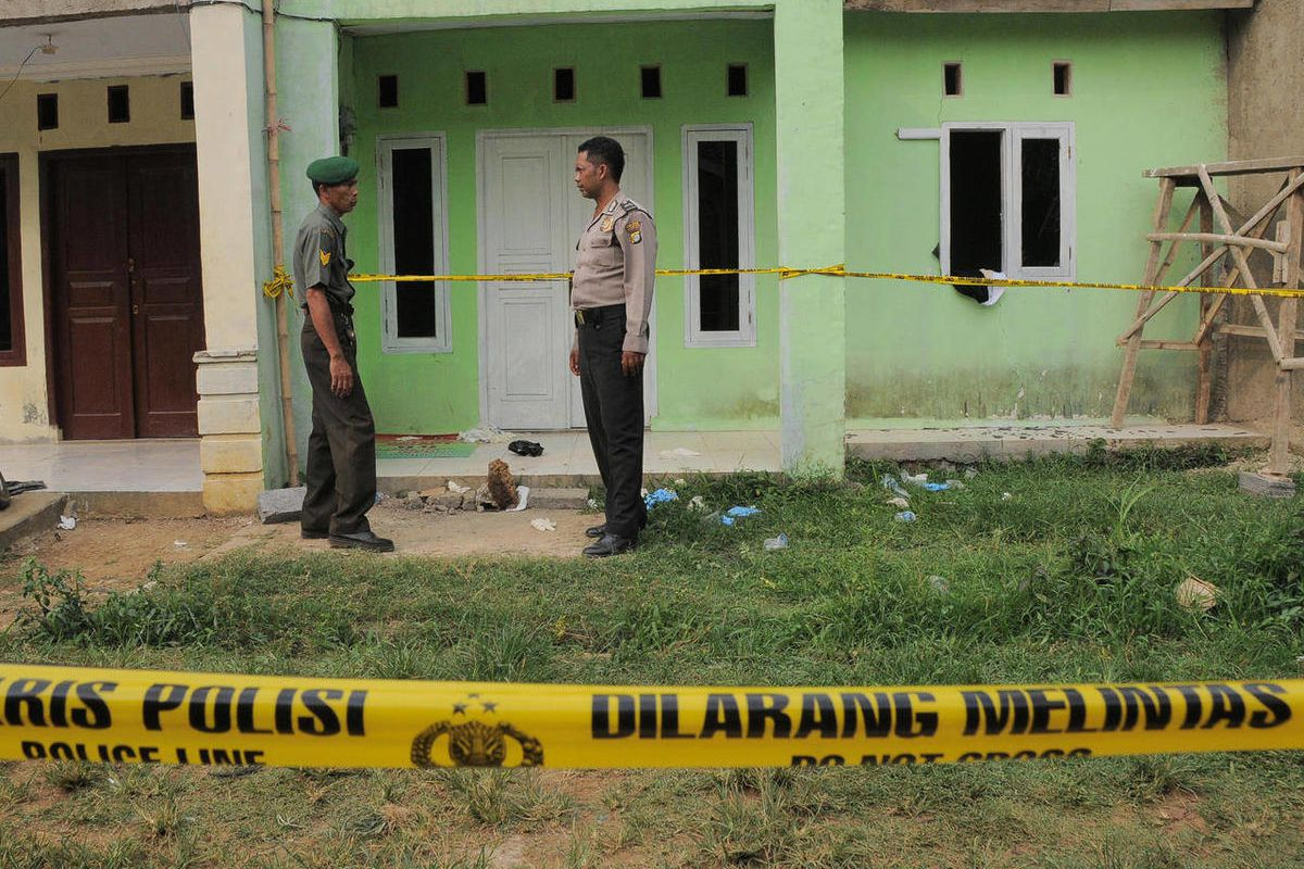 A police officer and a soldier stand guard outside the house of a suspected militant after a police raid in Bogor, West Java, Indonesia, Monday, Sept. 10, 2012.  Indonesia's anti-terrorism forces have been busy over the past few months closing in on milit