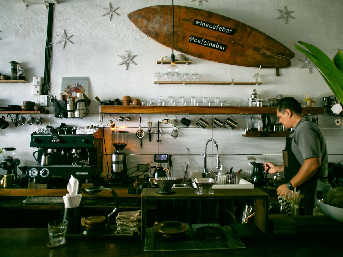 A man walks through the counter of a coffee shop with many coffee making tools and cups.