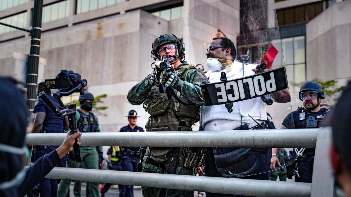 A protester holds a camera in front of a police officer in riot gear.