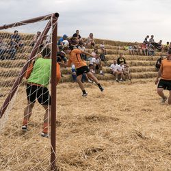 """In this photo taken on Saturday, June 4, 2016, people ply football at the arena, made of 4,500 straw bales, comes complete with tiered seating and flagpoles in Krasnoye, Stavropol region, South Russia. In a project straight out of the """"Three Little Pigs"""" fairytale, Roman Ponomarev has built a straw replica of the 643-billion-ruble ($700 million) stadium in St. Petersburg which will host World Cup semifinals. (AP Photo/Oleksandr Stashevskyi) ORG XMIT: XAZ128"""
