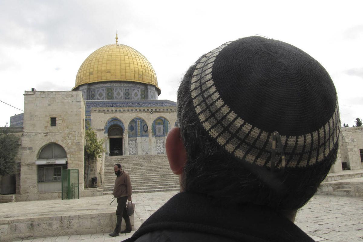 In this Monday, Dec. 9, 2013 photo, a Jewish man looks towards the Dome of the Rock in Jerusalem. The Jerusalem site, known to Muslims as the Noble Sanctuary and to Jews as the Temple Mount, is ground zero in the territorial and religious conflict between