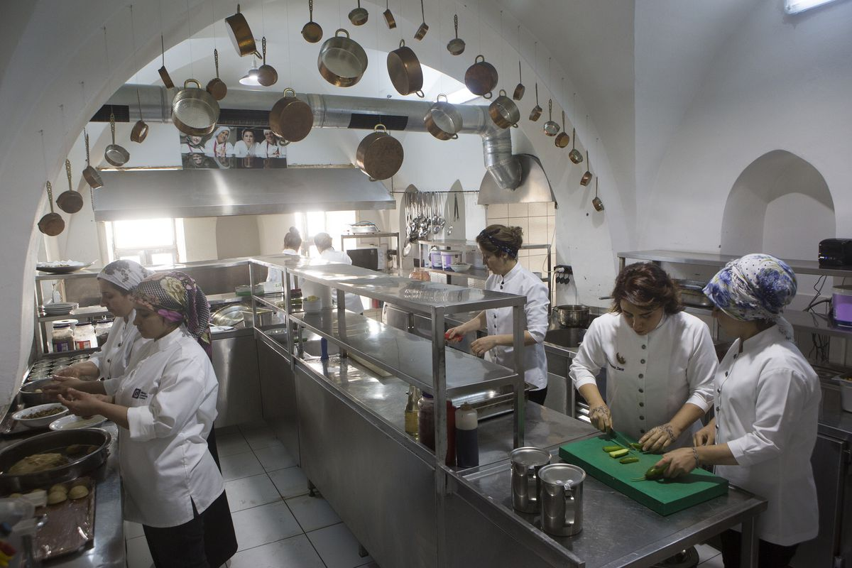 A kitchen in which women are engaged in various tasks