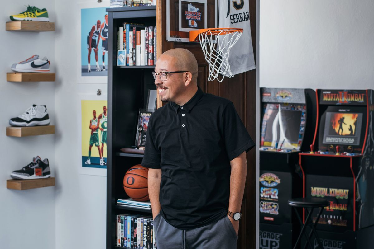 Author Shea Serrano standing with his hands in his pockets in front of a bookshelf, toy basketball hoop, and arcade-style video game machines.