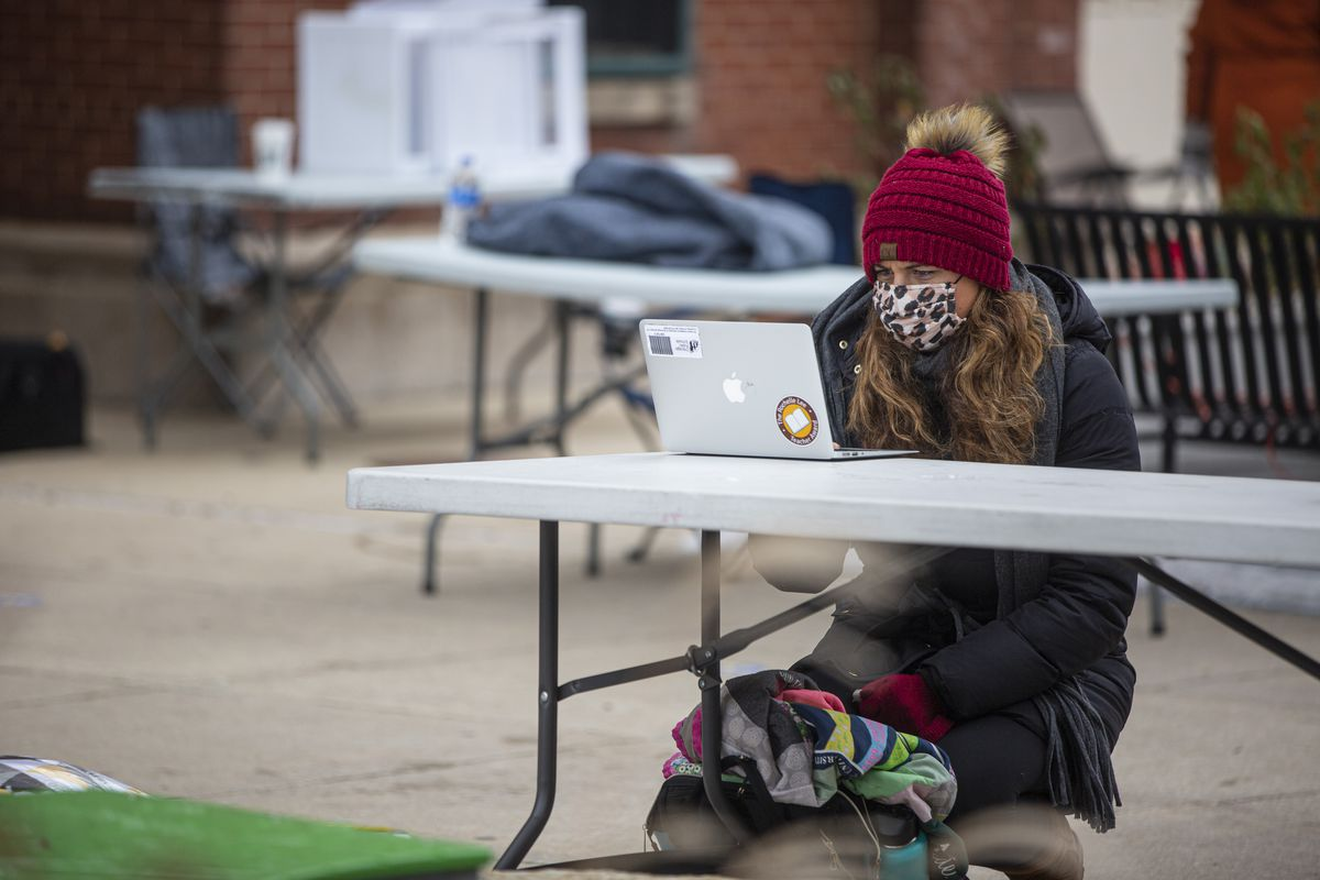 A school teacher works on a laptop outside during a protest against returning to in person teaching at Brentano Elementary School at 2723 N Fairfield Ave in Logan Square, Monday, Jan. 4, 2021.