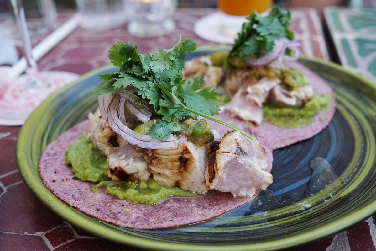 Grilled albacore tacos with crushed avocado on a green accented plate.