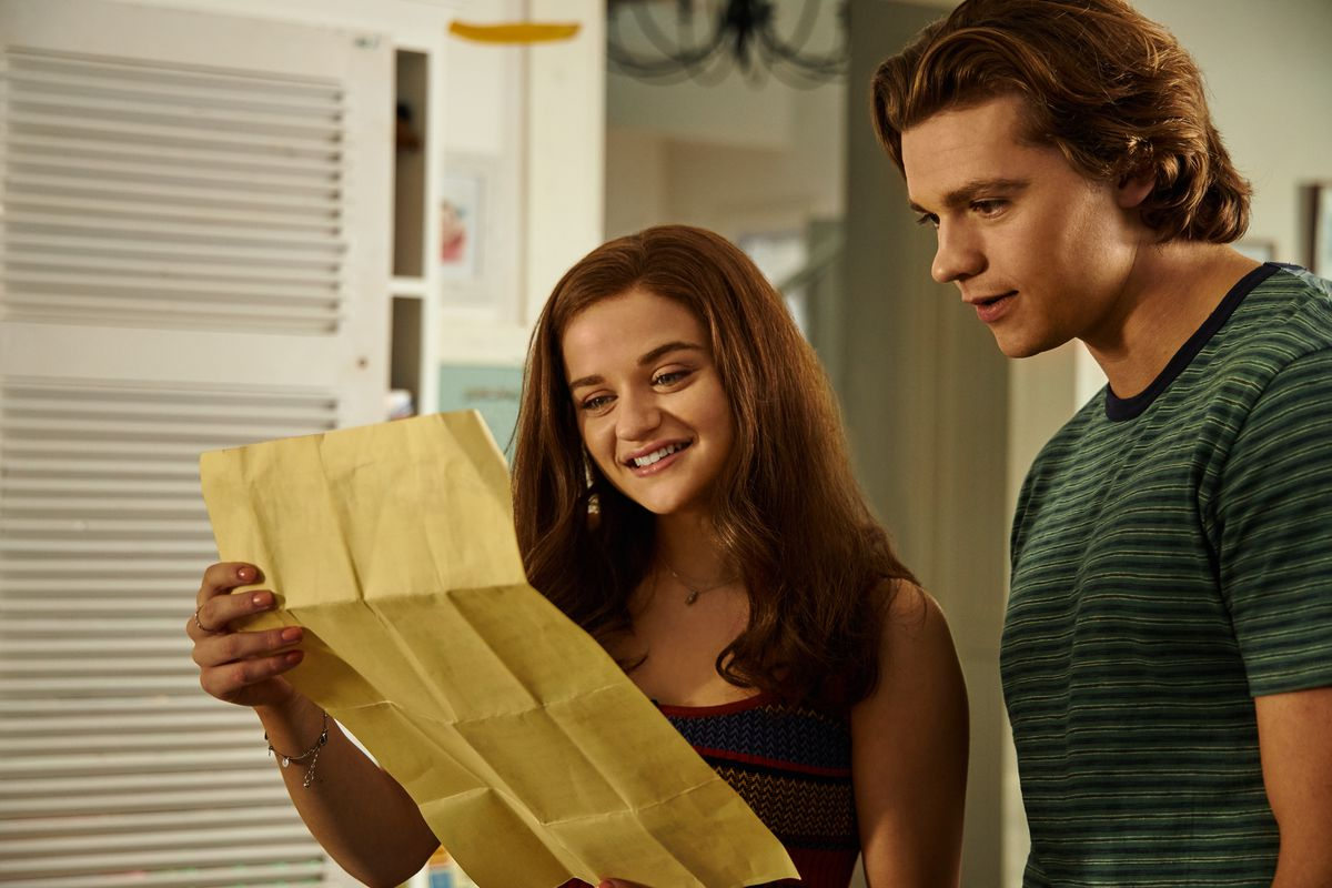 two teenagers looking at a college acceptance letter
