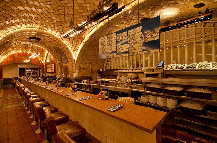 A long underground bar with backed bar stools is set up under an arching tunneled ceiling with yellow glowing lights.