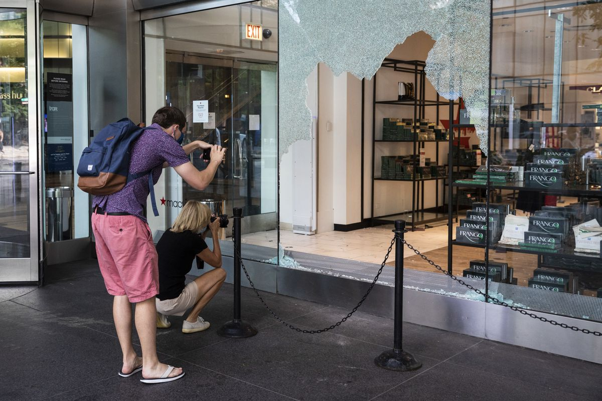 People take photos of the damaged Macy's at Water Tower Place, 835 N. Michigan Ave., on Monday after a night of looting.