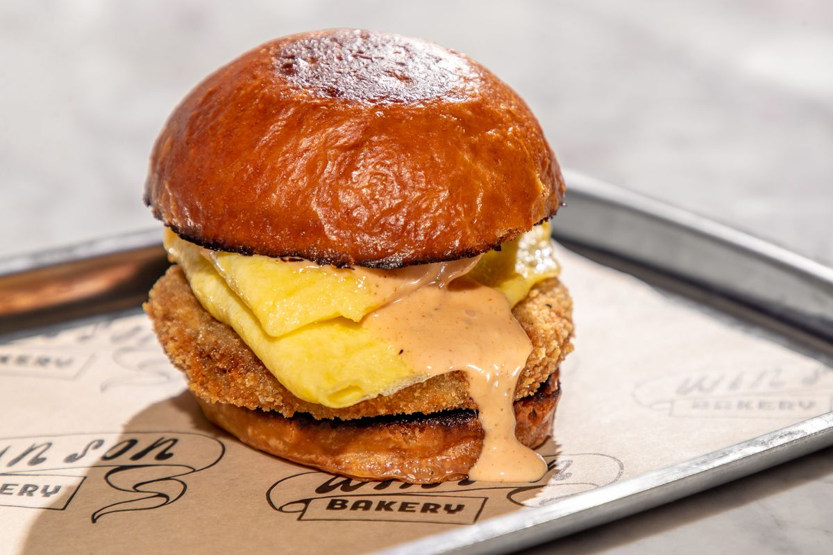 A pork knuckle egg sandwich with sauce dripping down the side