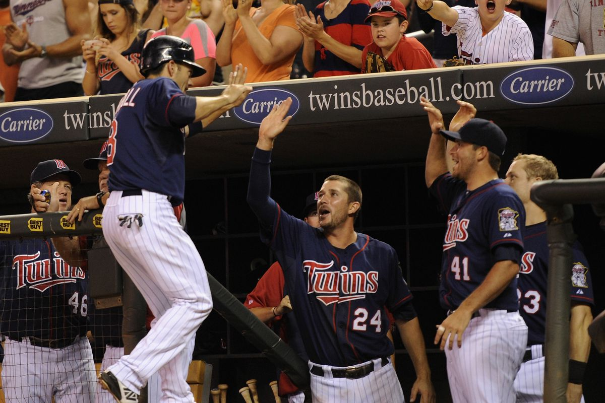 Trevor Plouffe congratulates Jamey Carroll on scoring the Twins' go-ahead in the bottom of the 7th as front-row fan furiously texts on.