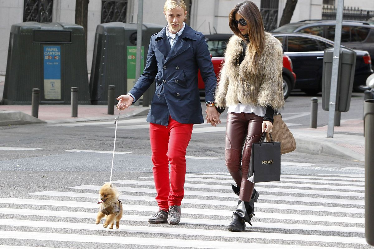 A man and woman holding hands walk a small dog on a leash