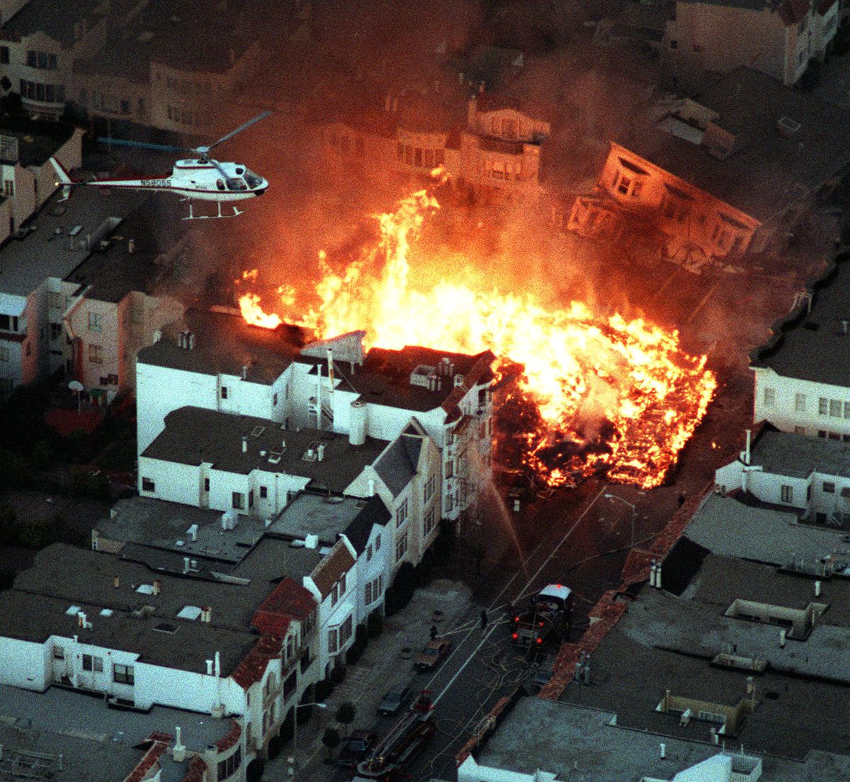 An aerial photo showing a massive fire happening in the middle of a residential neighborhood. A news helicopter hovers above.