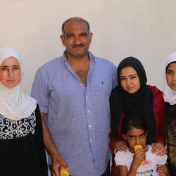Hanadi Al-Hamdan, left, her husband Farez, pose for a photo with three of their eight children in the Kyllini refugee camp near Myrsini, Greece, July 11, 2016. The Al-Hamdans fled civil war in Syria and have been living in the camp since March.