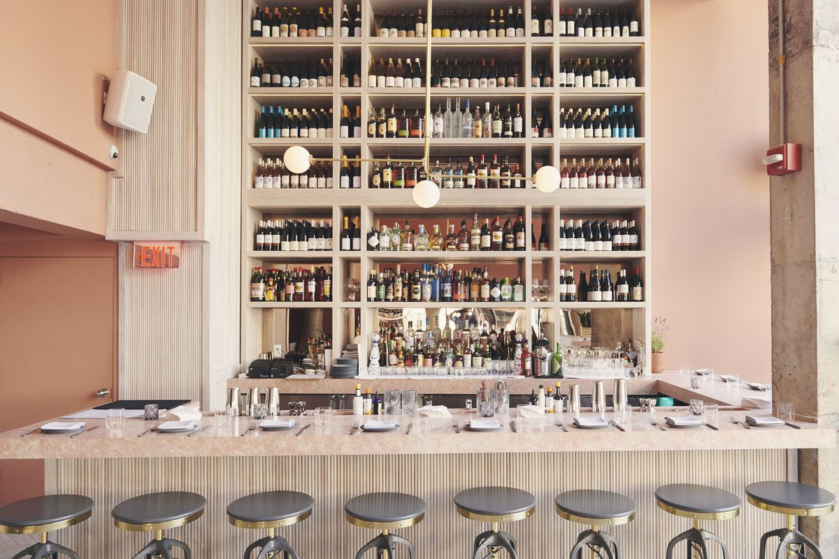 A bar with round stools and shelves with lots of bottles