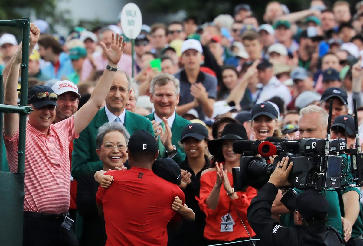 Tiger hugs his children, with his mom, Tida, over his left shoulder.
