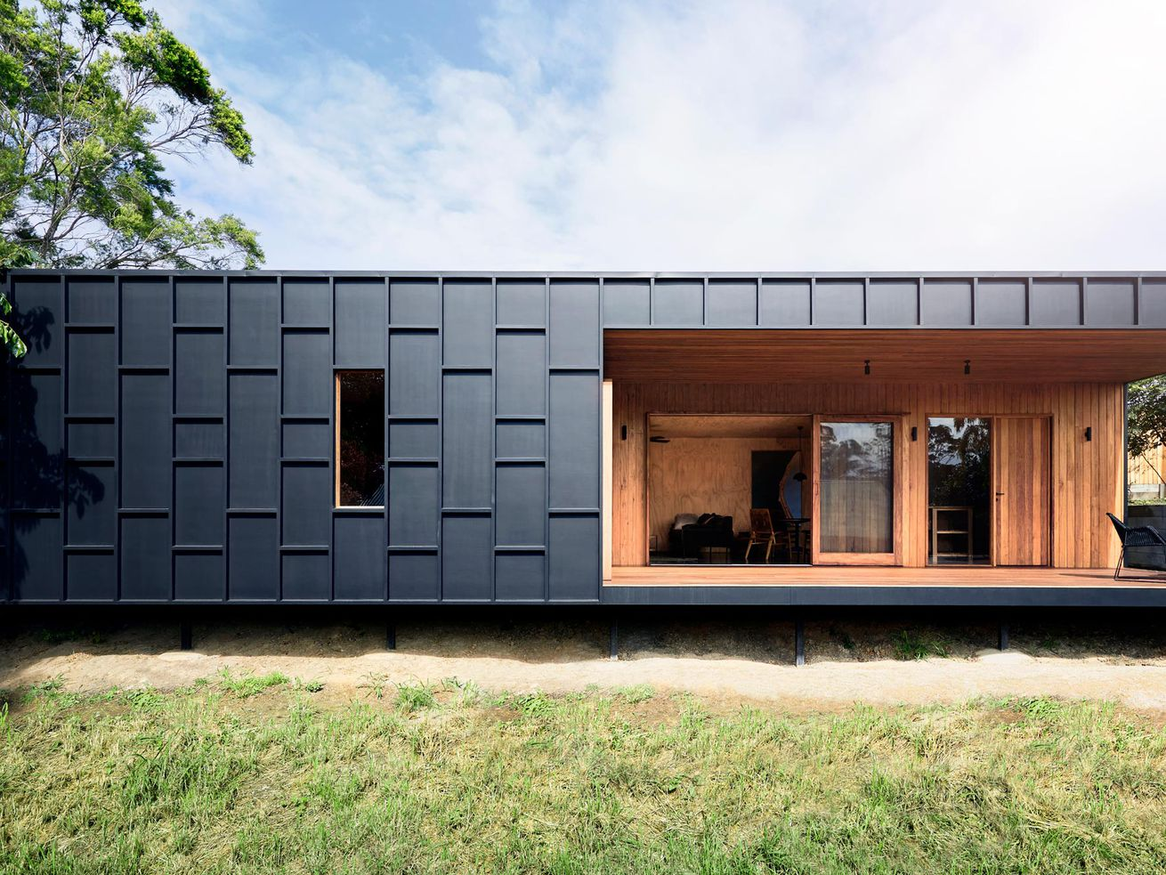 A single-story house featuring dark panel cladding and a cut-out opening to the interior, which is lined in plywood.