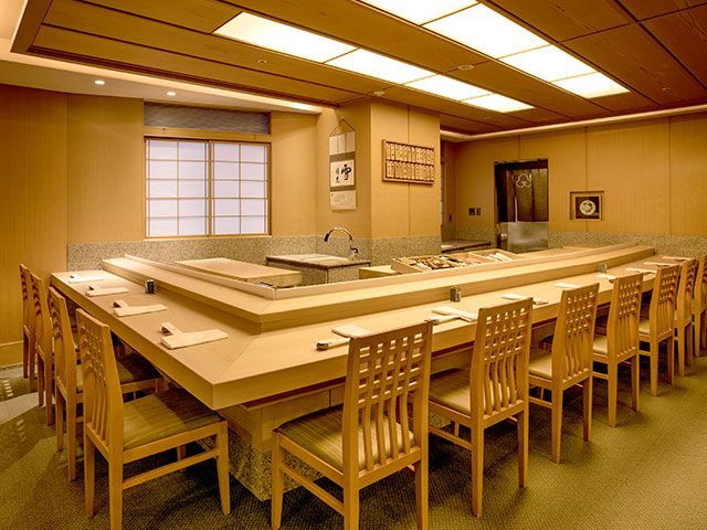 An empty L-shaped sushi counter surrounded by simple chairs in a dim, paneled room, with a screen door against one wall