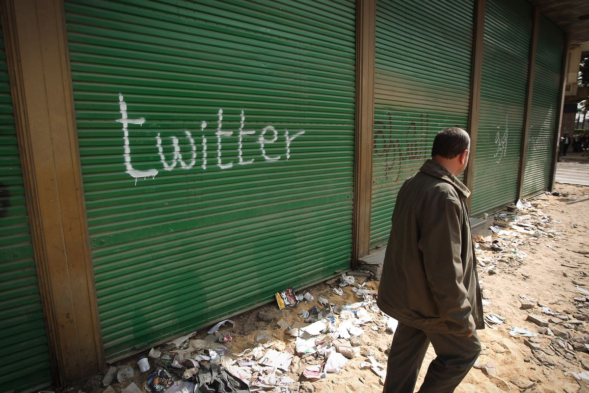 """The word """"twitter"""" is graffitied on a green roll-down door."""