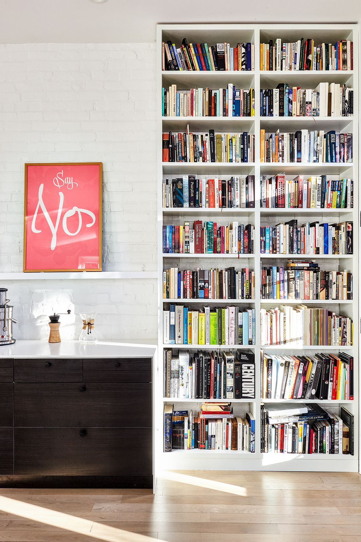 A room with a floor to ceiling bookcase full of books. Next to the bookcase is a black dresser. The wall is exposed painted white brick. There is a work of art hanging over the black dresser.