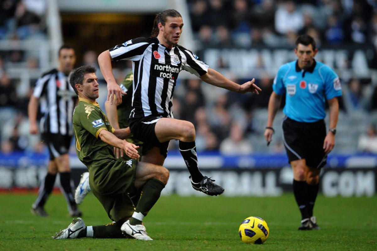 Andy Carroll of Newcastle vs Aaron Hughe of Fulham. Photo via Getty Images.